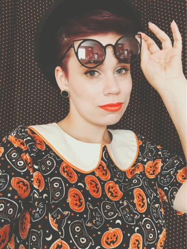 Mickey of Nerdily in a Halloween-themed dress in front of a black and orange polka dot background.