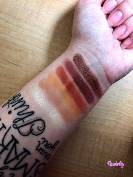 Wrist with five eyeshadow shades in red hue.
