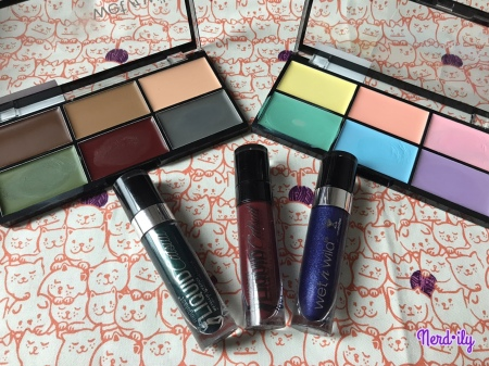 Three tubes of Wet n' Wild liquid lipstick with two cream color face paint palettes behind them.