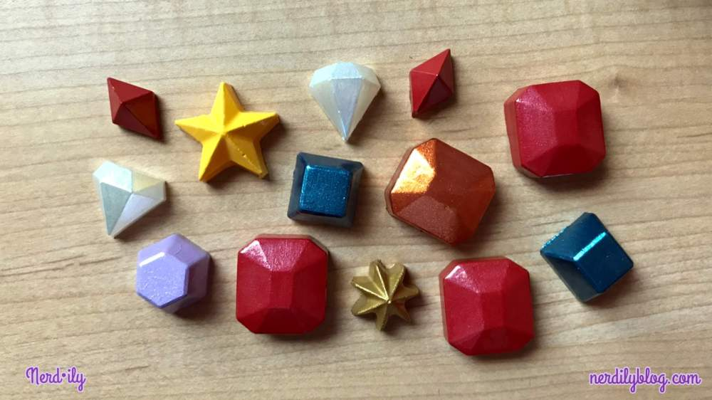 Various shapes in the form of gems and stars that are made out of hot glue and painted.