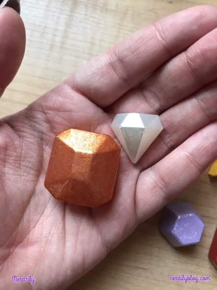 One orange square hot glue gem and one clear diamond-shaped hot glue gem in hand.