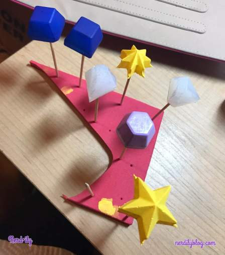 Different shapes of hot glue gems propped up with paint drying on them.