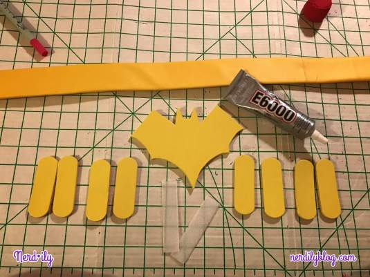 Yellow belt base on cutting board with a tube of E6000 glue, Batgirl symbol made of foam, and additional foam pieces.