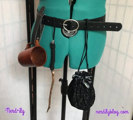 Belt on dressform with a tankard, drawstring bag, and wand attached.