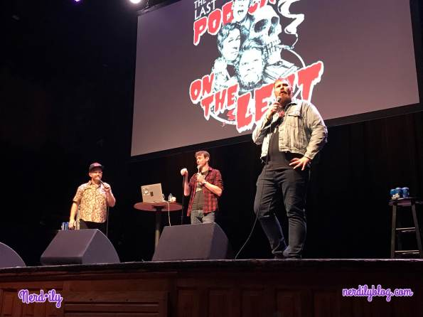 The three hosts of Last Podcast on the Left standing on a stage at a live performance.